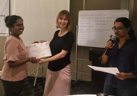 Karolina Mellor Presents a Workshop Participant with a Workshop Completion Certificate